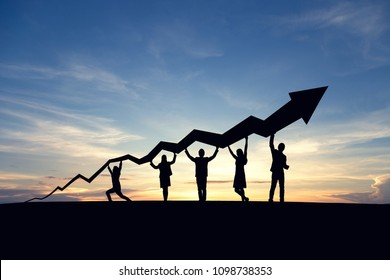 Silhouette of business people and graph at sky and sunset background.  Cooperate, success, teamwork and goal concept.