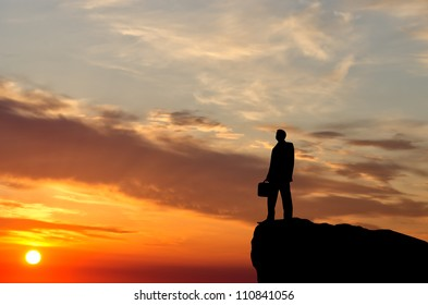 silhouette of a businessman with a briefcase in his hand is on top of the mountain against the sky.