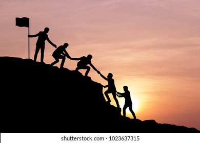 Silhouette of businessman helping each other hike up a mountain at sunrise. Business, teamwork, goal, success and help concept. Vintage filter.