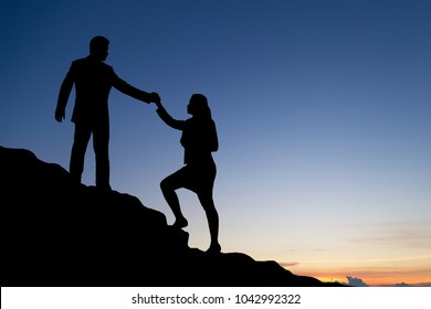 Silhouette of businessman helping each other hike up a mountain at sunrise. Business, teamwork, goal, success and help concept.