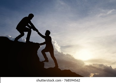 Silhouette of businessman helping each other hike up a mountain at sunrise. Business teamwork success concept. Vintage filter.