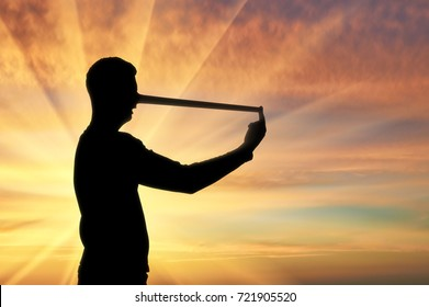 Silhouette of a businessman with a long nose that lies. The concept lies and deceit