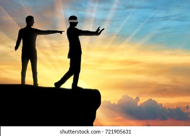 Silhouette of a businessman showing the way to a blind businessman in the abyss. The concept of meanness and treachery