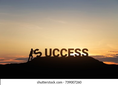 "Silhouette of businessman with the word ""success"" on mountain over sky and sunset background. - business, success and achievement concept."