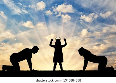 Silhouette of a child girl with a crown on her head and parents worshiping her. Conceptual image of childish egoism
