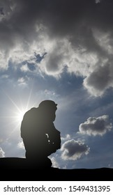 Silhouette of a Chimpanzee crouching against a surreal cloudy sky.