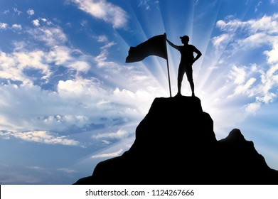 Silhouette of a climber with a flag on top of a mountain. Conceptual scene of success