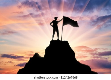 Silhouette of a climber with a flag on the top of the mountain which he subdued. Conceptual Scene