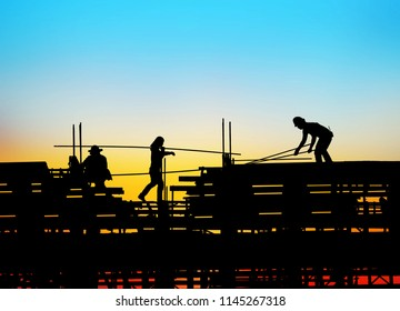 silhouette construction team working on high ground over blurred background sunset sky.