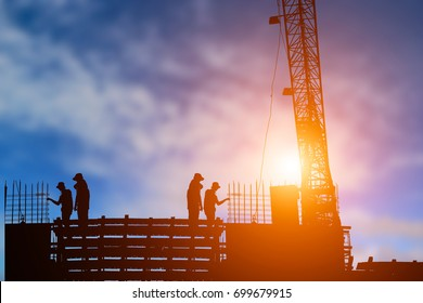 silhouette construction team working on high ground over sky blurred background