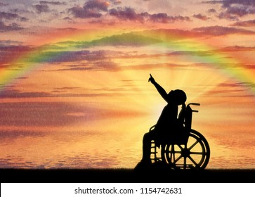 Silhouette of a disabled child girl sitting in a wheelchair showing a finger at a rainbow against a sea sunset background. Conceptual image of the life of children with disabilities