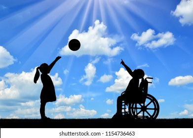 Silhouette of a disabled child girl in a wheelchair and healthy girl playing in a ball outdoors. The concept of children with disabilities in a society of healthy children