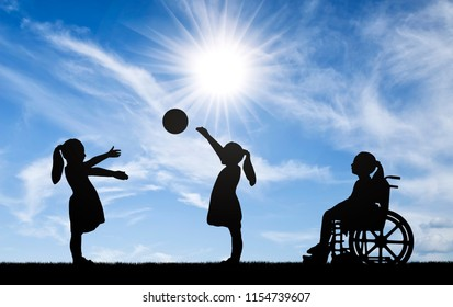 Silhouette of a disabled child girl in a wheelchair looking away as healthy children play in a ball outdoors. The concept of children with disabilities in a society of healthy children