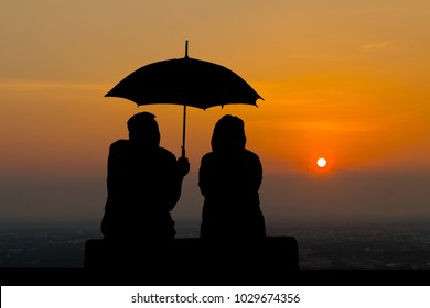 Silhouette the elderly are spread umbrella to couple at sunset background.