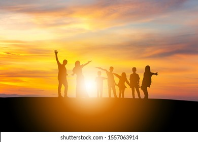 Silhouette of a Family with children and friend playing with sunset background.