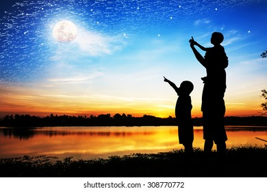 Silhouette of father use hand point his son look at full moon on the sky