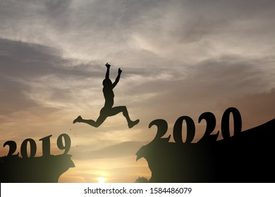 Silhouette of a female athlete leaping across a gorge from 2019 to 2020 for the New Year concept: leaping into the New Year 2020.