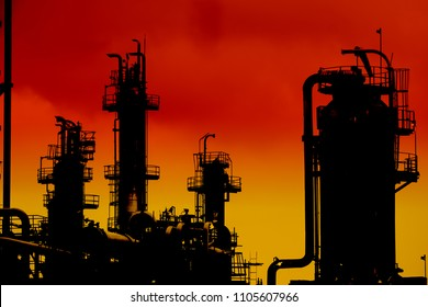 Silhouette of gas distillation tower and pipeline on sunset sky background