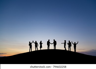 Silhouette group of business man and woman celebrating success on top mountain, sky and sun light background. Vintage filter. Business, successful, leadership, achievement and goal concept.
