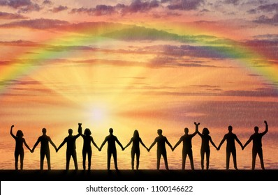 Silhouette of a group of happy people holding hands by the sea at sunset with a rainbow. The concept of mutual assistance and support in people