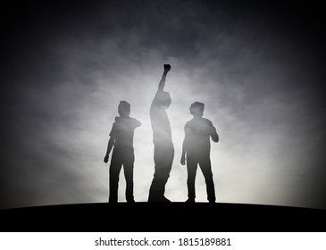 Silhouette of a group of young man raising their fist in defiance against a surreal smoky landscape for the concept of protesting under duress.