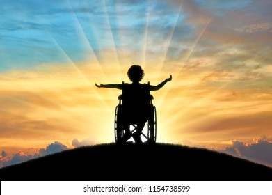 Silhouette of a happy disabled child girl sitting in a wheelchair atop a hill at sunset. Concept of happy children with disabilities