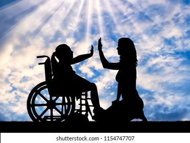Silhouette of a happy disabled child girl sitting in a wheelchair doing hand gesture, give five to her mom. The concept of support for children with disabilities