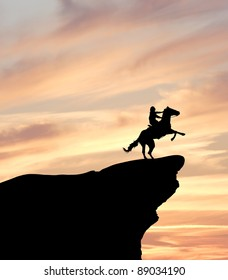Silhouette of a horse rider on a cliff at sunset.