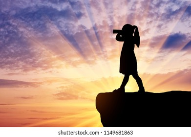 Silhouette of little girl child standing on top looking through binoculars. The concept of children's curiosity and discovery
