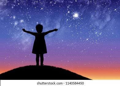 Silhouette, little happy girl child standing on a hill looking not starry beautiful sky. Conceptual image