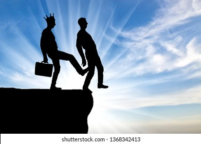 Silhouette, A male egoist with a crown is pushing another man into the abyss with his foot. Concept of selfishness and betrayal in business