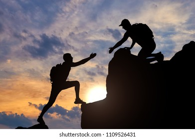 Silhouette of a male mountaineer working in a team with a partner, giving him a helping hand. The concept of a helping hand