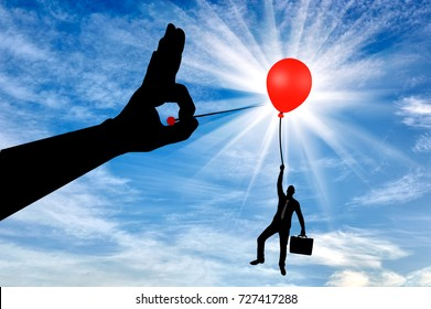 Silhouette of a man in the air clinging to a balloon and a hand with a needle wants to burst it. The concept of meanness and treachery in business