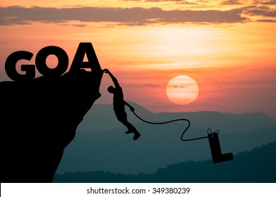 Silhouette Man climbs into cliff to make the word GOAL setting concept