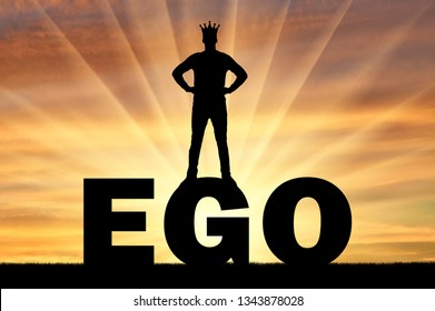 Silhouette of a man with a crown on his head standing on the word ego against the backdrop of a sunset. Concept of selfishness