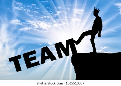 "Silhouette of a man is an egoist with a crown on his head, he pushes the word ""team"" into the abyss. Concept of selfishness, individual"