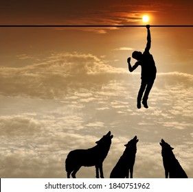 Silhouette of a man hanging on to a tightrope with a pack of menacing dogs at his feet for the concept of hanging on for his life.