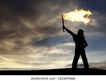Silhouette of a man holding a flaming torch above his head to signal for attention.