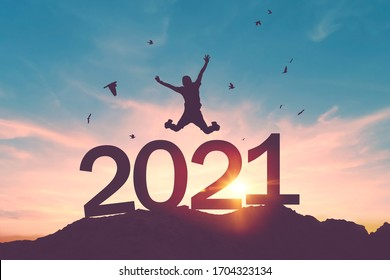 Silhouette man jumping and birds flying on sunset sky at top of mountain and number 2021 abstract background. Happy new year and holiday celebration concept. Vintage tone filter color style.