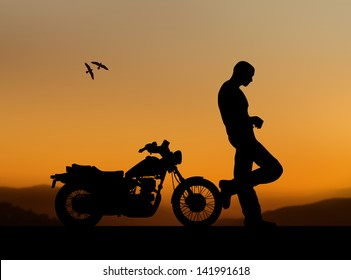 silhouette of a man with a motorcycle on a sunset background
