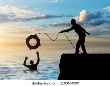 A silhouette of a man throws a lifeline to another man who is drowning in the water. The concept of mutual assistance in a business team