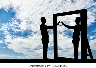 Silhouette of a narcissist man and a hand gesture of a heart in reflection in a mirror. The concept of narcissism and selfishness