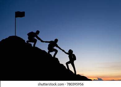 Silhouette of people helping each other hike up a mountain and sunset background. Business, teamwork, success, help and goal concept.
