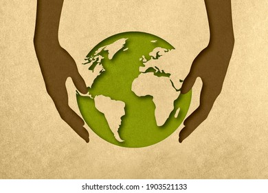 The silhouette of the planet in the arms of the hands in the style of paper clippings. Ecological concept. The green planet. Earth Day. Mother Nature. Recycling. Biodegradable material.