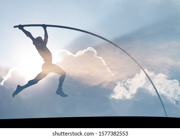 Silhouette of a pole vaulter vaulting across a surreal azure sky for the concept of hardwork propelling to success.