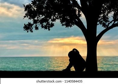 Silhouette of sad little girl sitting under a tree by the sea crying. Conceptual image of parents' divorce