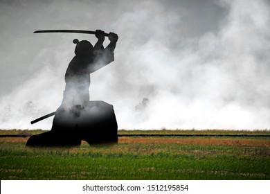 Silhouette of a Samurai Warrior raising his katana sword in the battle ground. Double exposure composite.