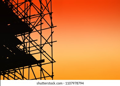 Silhouette of scaffolding on sunset sky background
