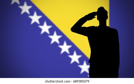 Silhouette of a soldier saluting against the bosnia flag