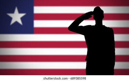 Silhouette of a soldier saluting against the liberia flag